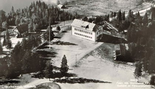 Svartvitt foto på en vit skolbyggnad med en öppen grusplan framför, omgivet av granskog.