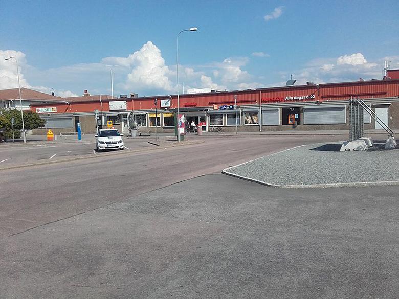 Ödslig parkeringsyta med låg affärsbyggnad i bakgrunden.