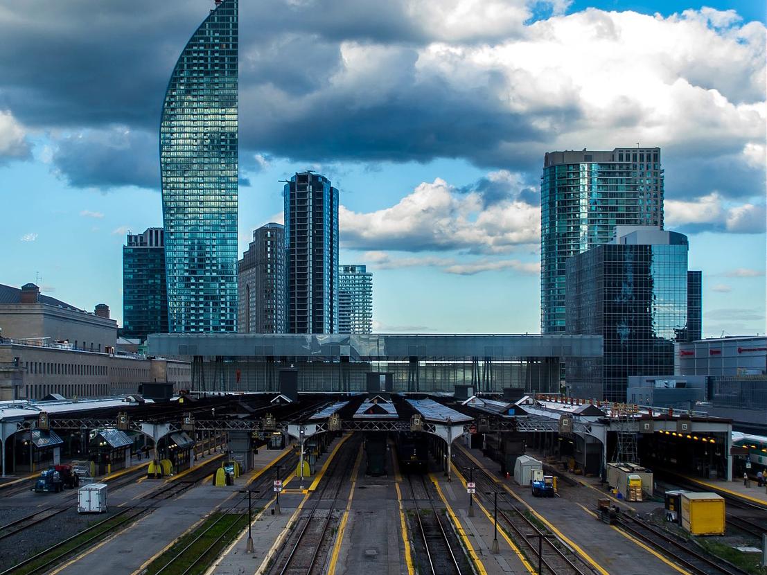 Räls som leder in mot en tågstation, med skyskrapor i bakgrunden.
