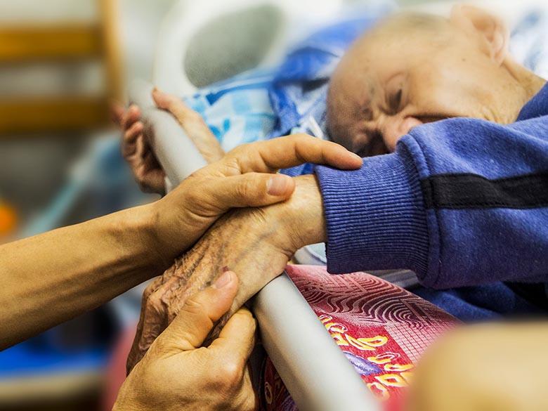 Äldre person ges omsorg av två händer.