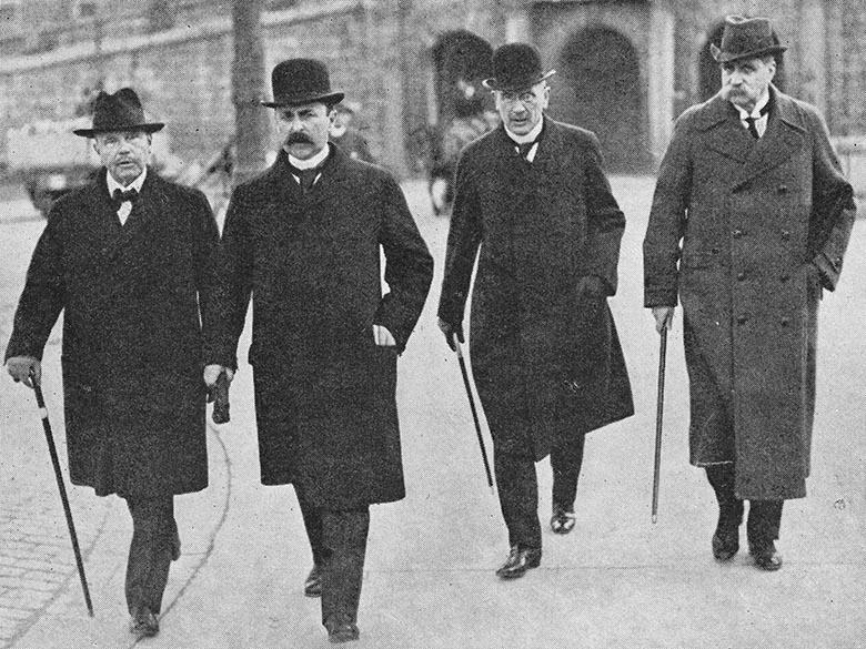 Svartvitt foto på tre män i rockar, hattar och med promenadkäppar.