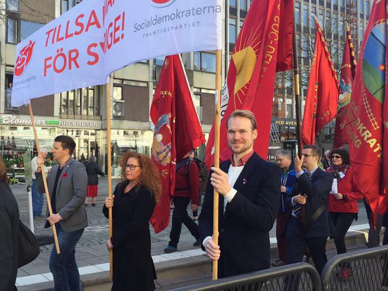 Tre personer bär Socialdemokraternas banderoll i första maj-tåg.