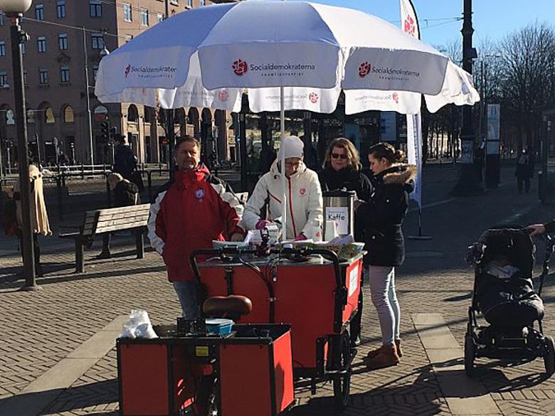 Fyra socialdemokratiska partifunktionärer står vid en vagn på Järntorget i Göteborg.