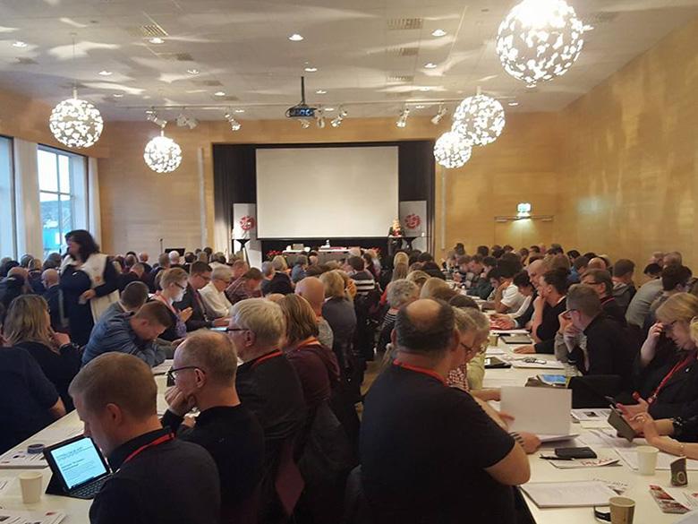 Ett stort antal människor sitter samlade vid mötesbord i kongressal.