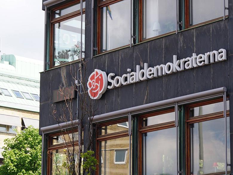 Socialdemokraternas logotyp mot en husfasad.