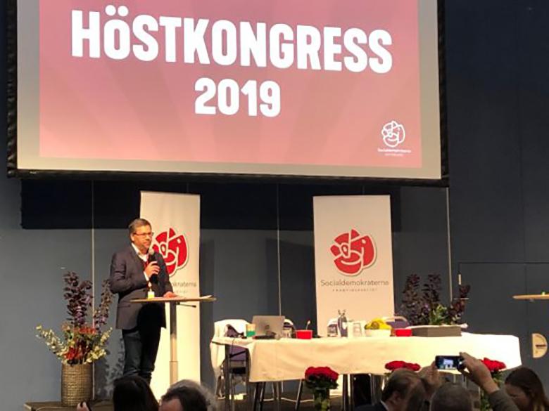 Mattias Jonsson står på en scen, framför texten Höstkongress 2019.