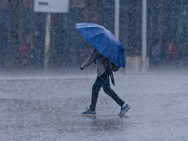 En person med paraply går genom hällregn.