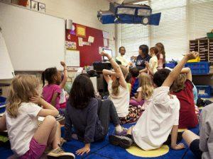 Barn på golvet i ett lågstadieklassrum.